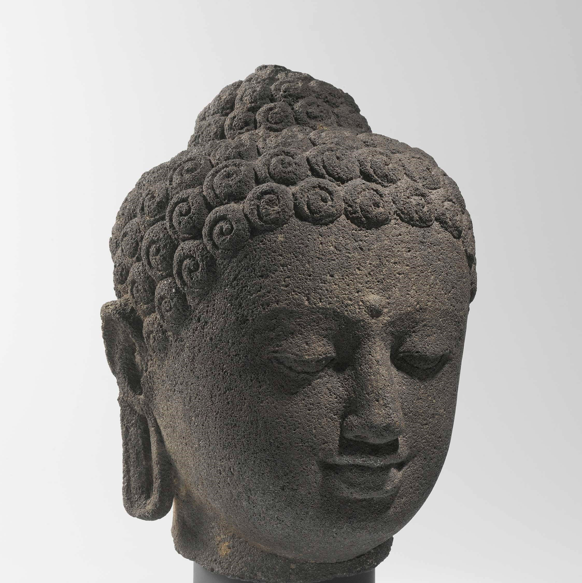 This andesite head of a Buddha is probably one of the 504 Buddha statues placed on and around the great Buddhist monument of Borobudur.