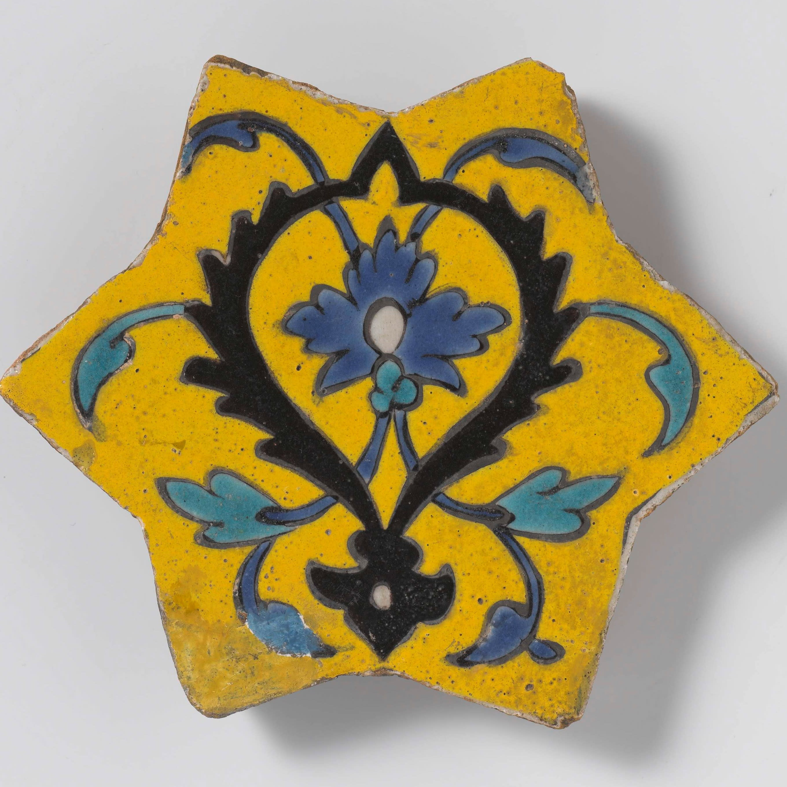 A star-shaped fritware tile decorated with floral scrolls in black, blue, and turquoise on a yellow background.
