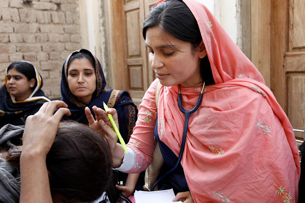 This image shows a female doctor with the International Medical Corps examines a woman patient at a mobile health clinic in the village of Goza.