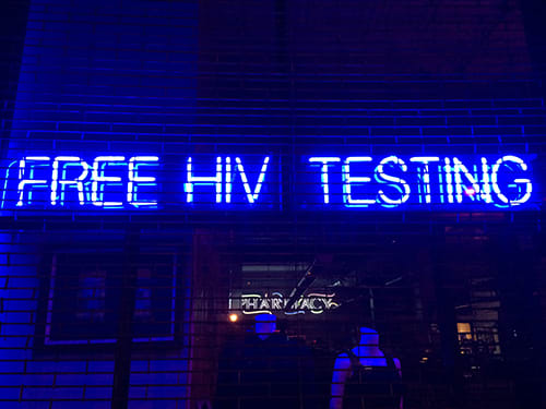 Photo showing 'Free HIV Testing' spelled out in blue & white neon letters hanging in a storefront window behind security gates in Boerum Hill, Brooklyn, NYC.
