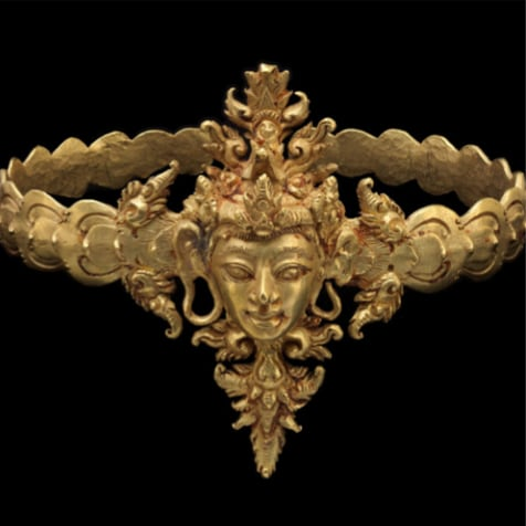 Image showing an Indonesian tenth century gold armlet. The band is formed by a row of overlapping lotus petals. The centre is decorated with a male face.