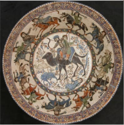 Image showing a Stonepaste bowl decorated with human figures and animals. In the centre, Prince Bahram Gur and his favourite mistress Azada are depicted hunting. Below the animal's paws is a depiction of the moment he crushes her.