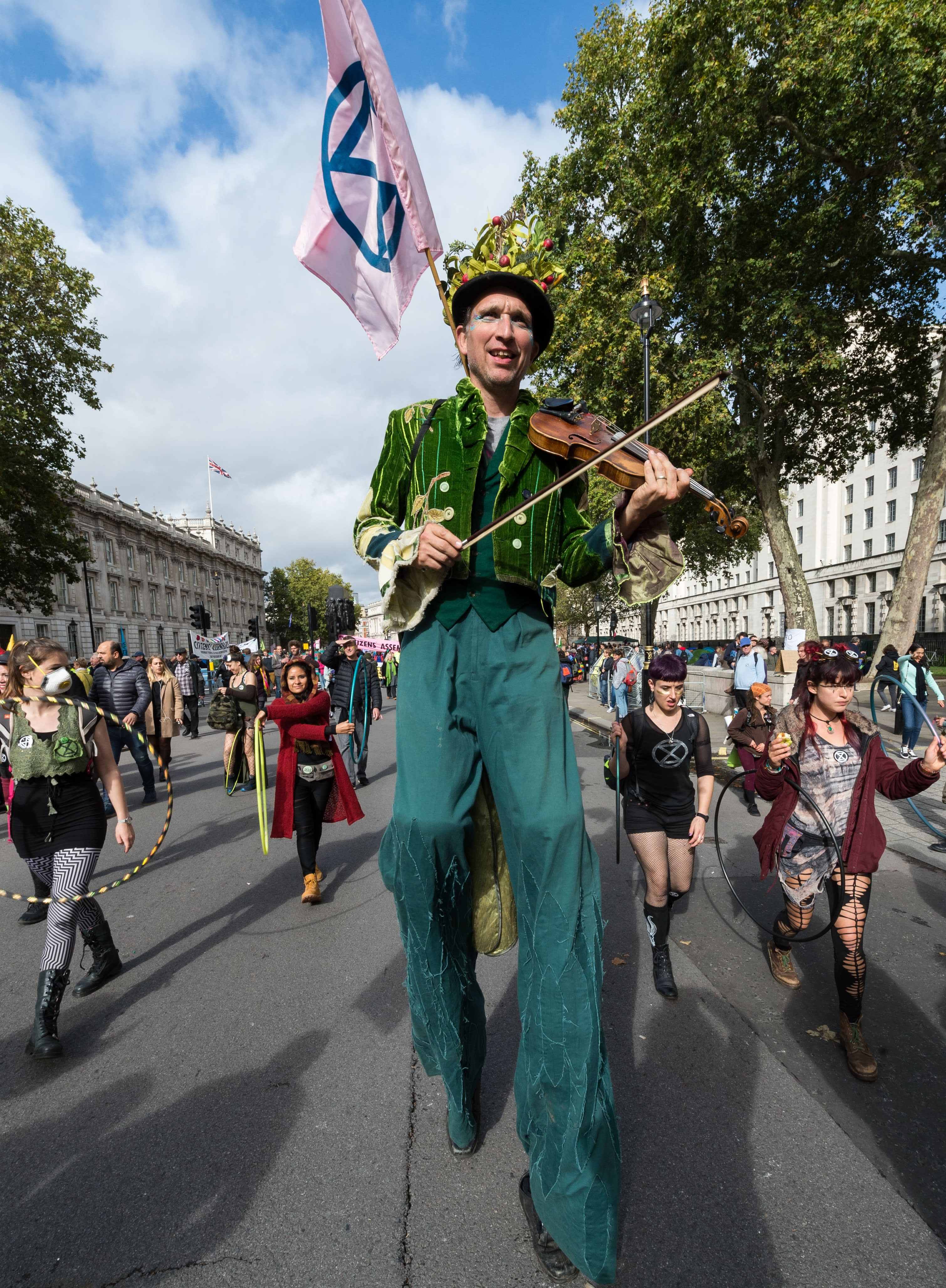 Environmental activist from Extinction Rebellion walks on stilts and plays the violin in London (Getty Images)