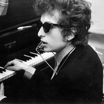 Bob Dylan plays piano with a harmonica around his neck during the recording of the album 'Highway 61 Revisited' in Columbia's Studio A in the summer of 1965 in New York City