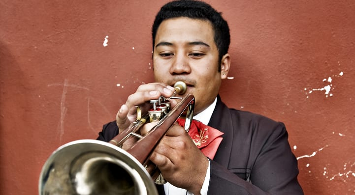 Mexican Mariachi man playing trumpet against a wall