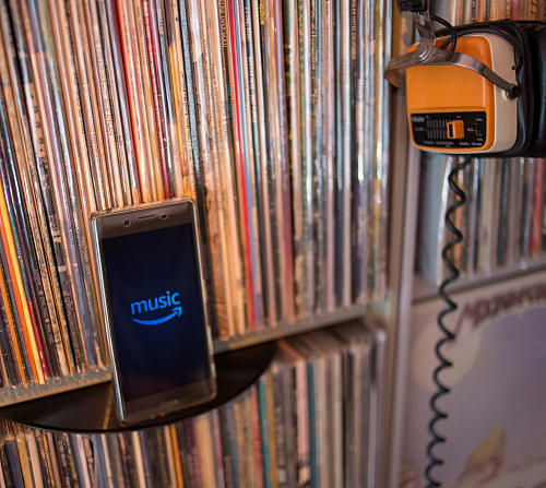 Amazon Music application displayed on an Android Sony smartphone in front of old 33rpm vinyls. (Photo Illustration by Guillaume Payen/SOPA Images/LightRocket via Getty Images)