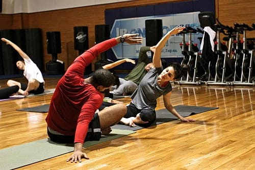 A view of people performing warm up exercises on a gymnasium floor