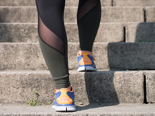 View of a woman's legs walking up a flight of steps in running attire