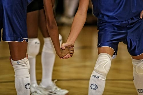 Two volleyball players hold hands before a point