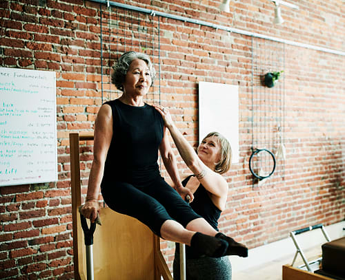 A female pilates instructor assisting mature student on high-low chair during class in exercise studio