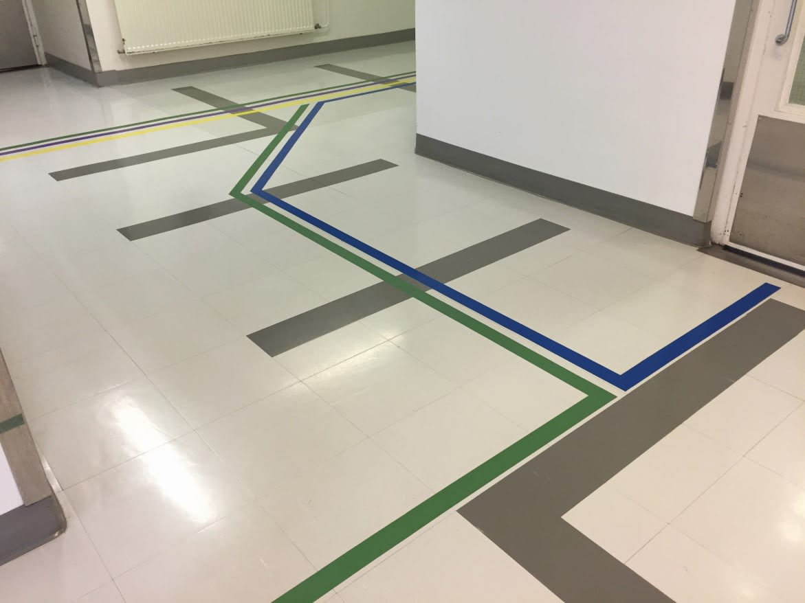 Wayfinding placed into the floor design using a color-guided pattern to orient and move visitors and patients through this medical space. Helsinki, Finland