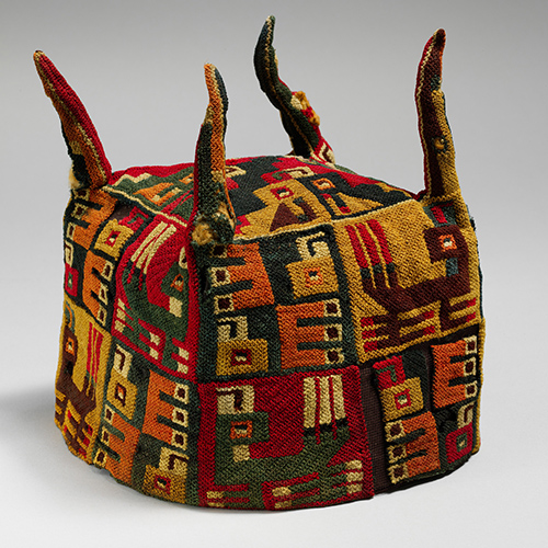Four-cornered hat decorated with geometric designs and stylized images depicting anthropomorphic figures, animals, and plants central in Wari and Tiwanaku religions.
