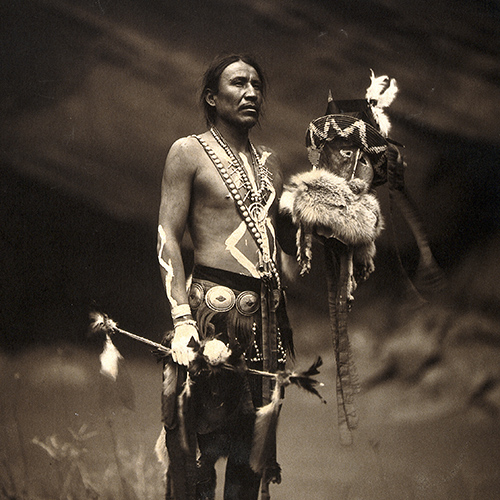 This photograph shows a Navajo man in ceremonial dress representing the Yebichai god Zahabolzi.