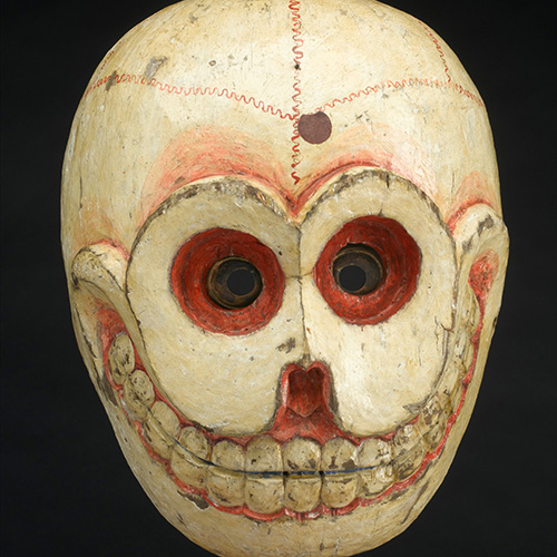 This is an image of a wooden mask with a smiling skull carved and painted onto it.