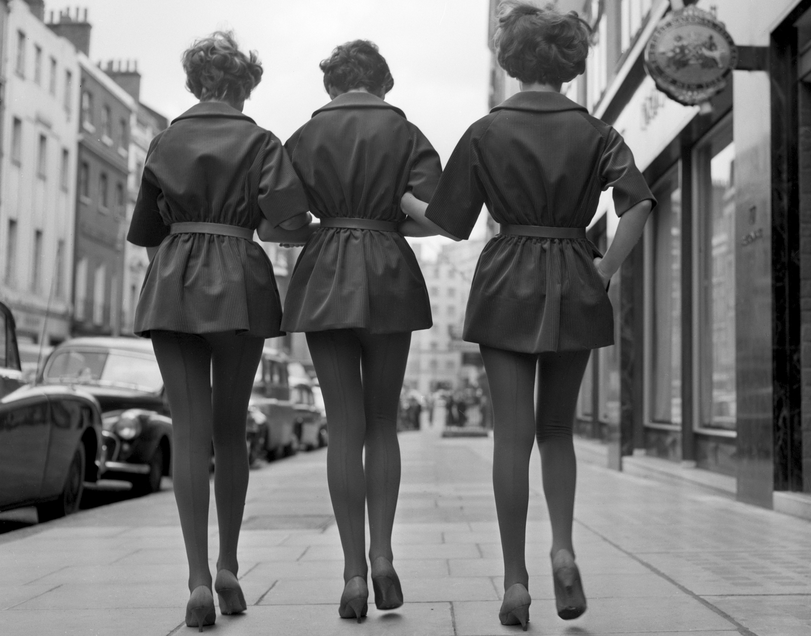 A black and white photograph showing teenage girls walking in beat-style outfits.