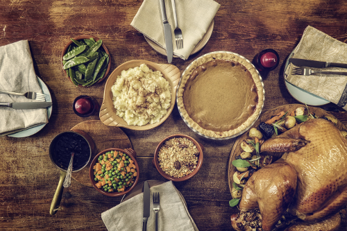 Traditional holiday dinner with stuffed turkey, mashed potatoes, cranberry sauce, vegetables and pumpkin pie.