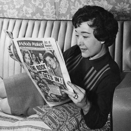 English singer Sheila Buxton reads music magazine 'Melody Maker' at her home in 1958