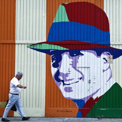 A man walks past an image of Carlos Gardel painted on a wall in Buenos Aires