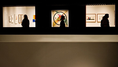 A woman passes circles in a circle by russian painter Wassily Kandinsky on the wall of barbican centre