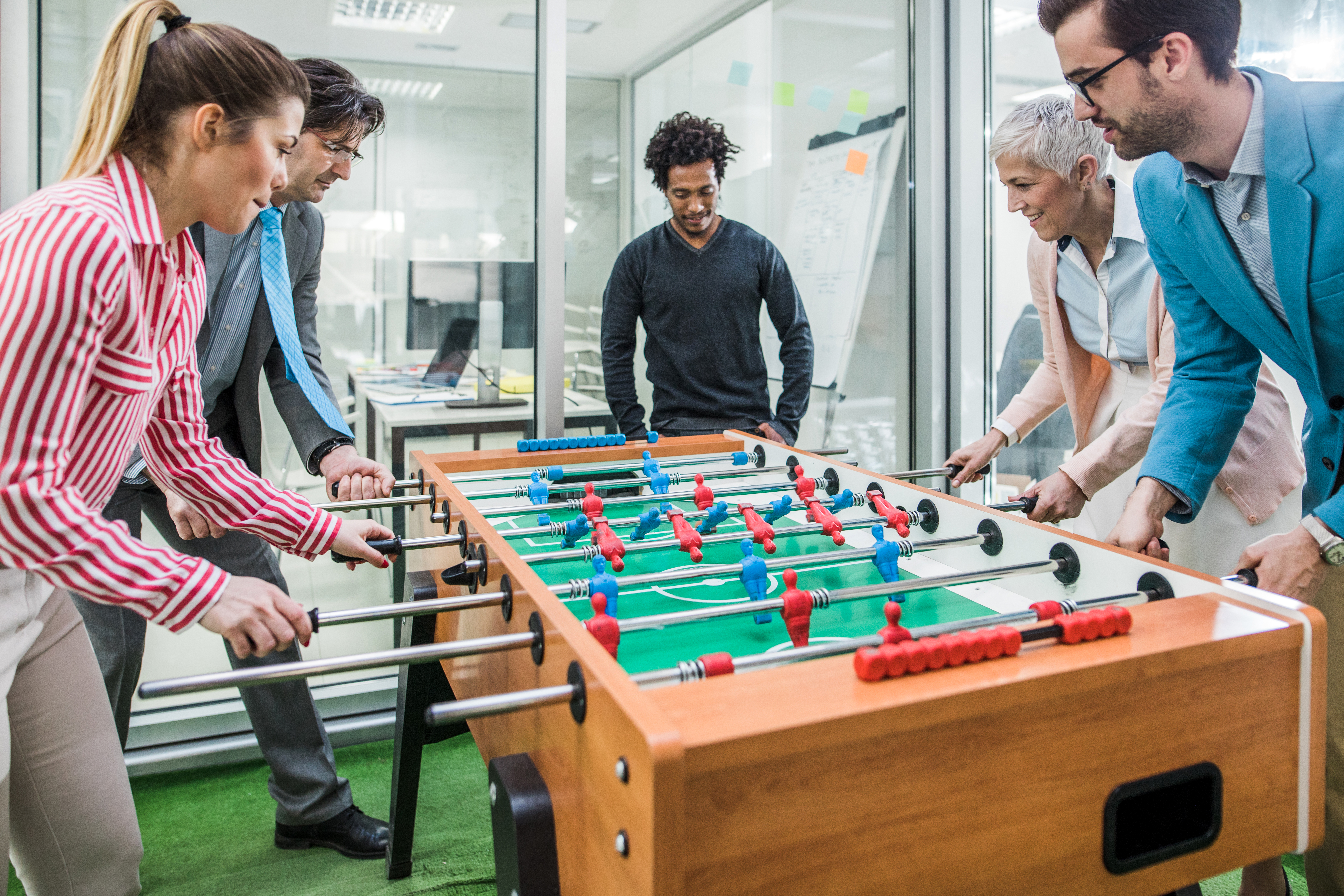 A Stock Photo of a team of happy entrepreneurs having fun on a break while playing table soccer.