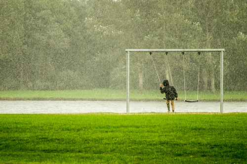 Person in a black hoodie riding a swing in the rain