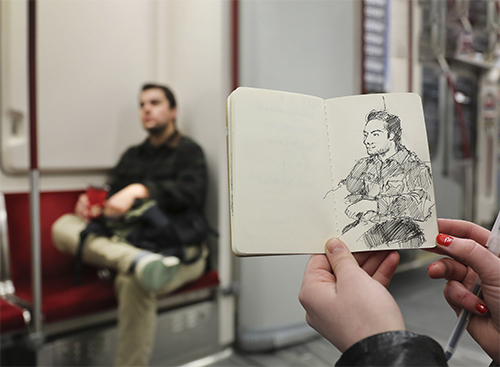 Someone sketches a person on the subway