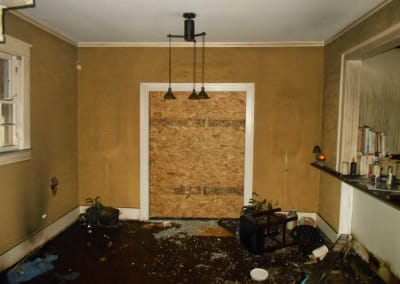 Dining room after a fire with debris everywhere and a boarded up entry