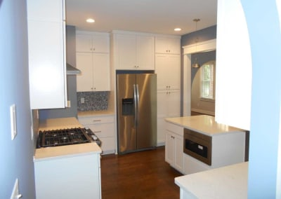 Modern renovated kitchen with white cabinets and stainless steel appliances. This was renovated after a fire destroyed the house.