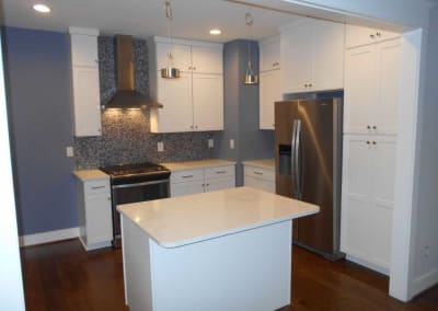 Modern renovated kitchen with blue walls and white cabinetry. This was renovated after a fire destroyed the house..