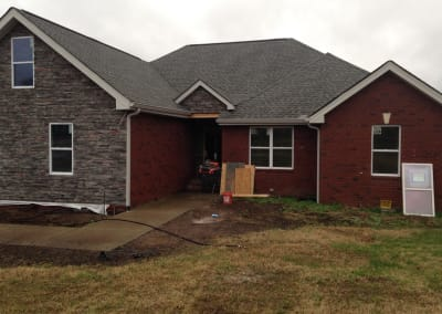 Stone and red brick home during the renovation stage after a complete fire loss