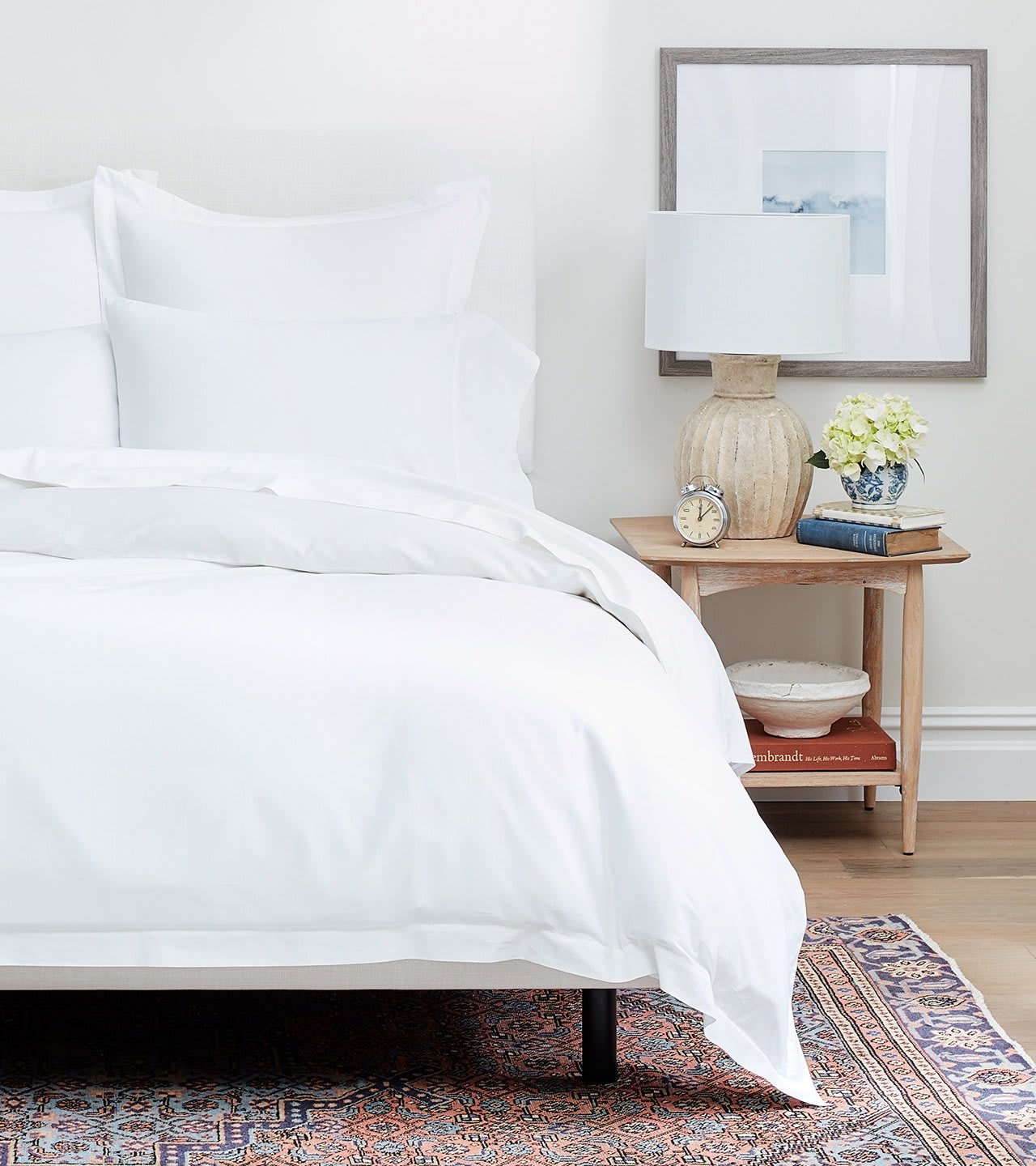 Image of a bed made with white bed sheets