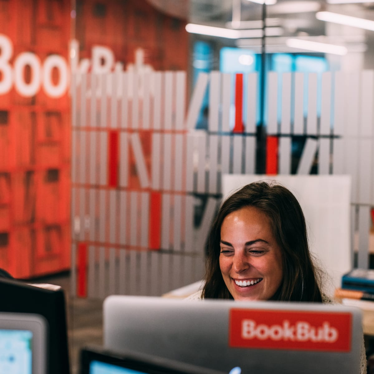 A BookBub employee sits at her computer in the BookBub office, smiling.