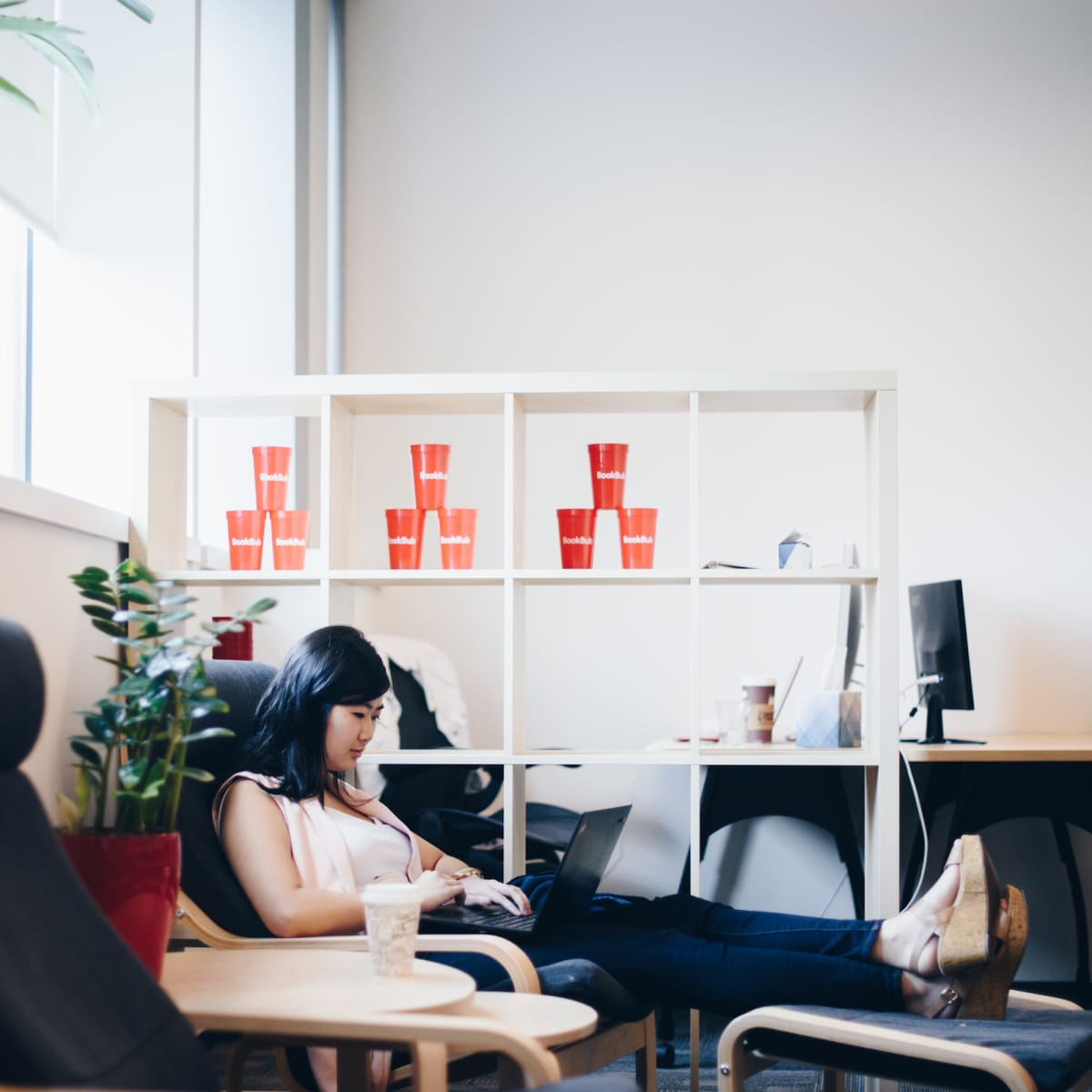 A BookBub employee sits in the quiet room in the office, working in a comfortable chair.