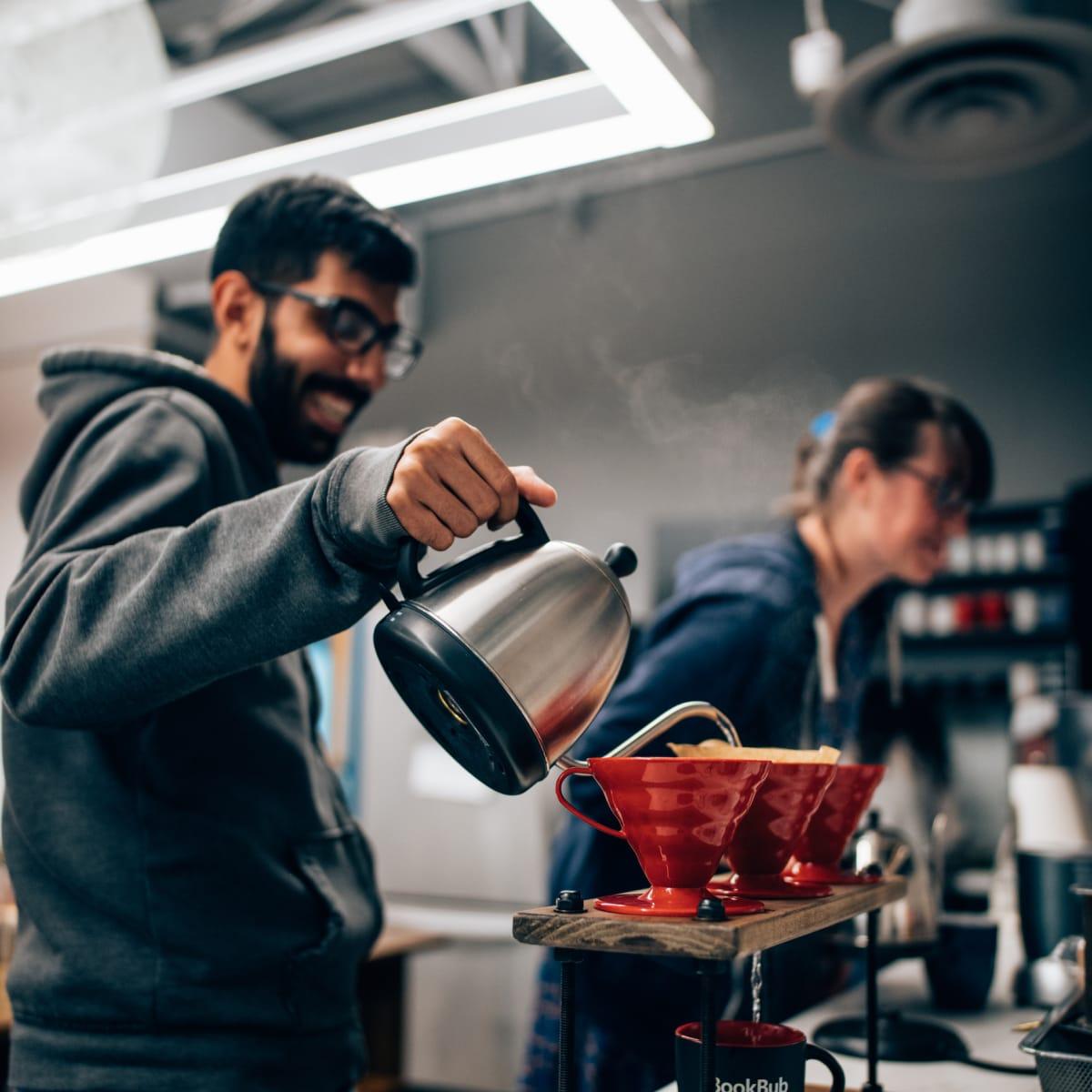 "BookBub employees prepare pourover coffee in the ""cantina,"" a social area in the BookBub office."