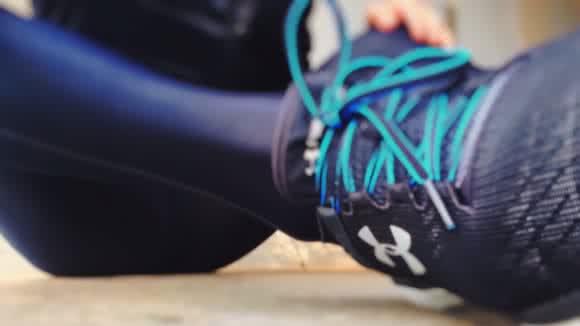 Une personne fine est assise sur le sol, en tenue de sport. L'objectif se focalise sur sa chaussure droite, qui semble être une chaussure de running.