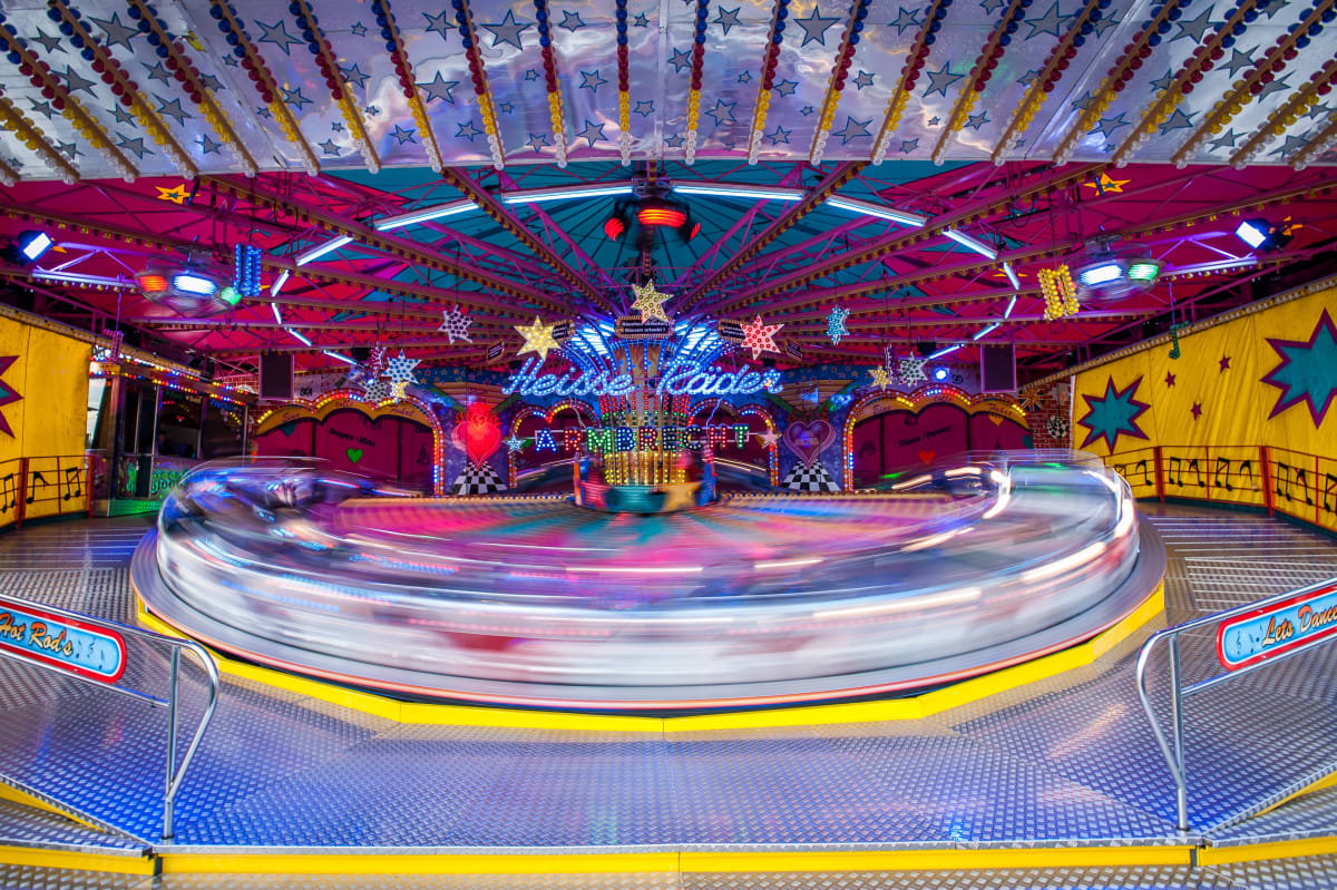 Photo of a carousel in action. The rotational movement creates a fuzzy effect: it is impossible to know with certainty the speed of the merry-go-round.