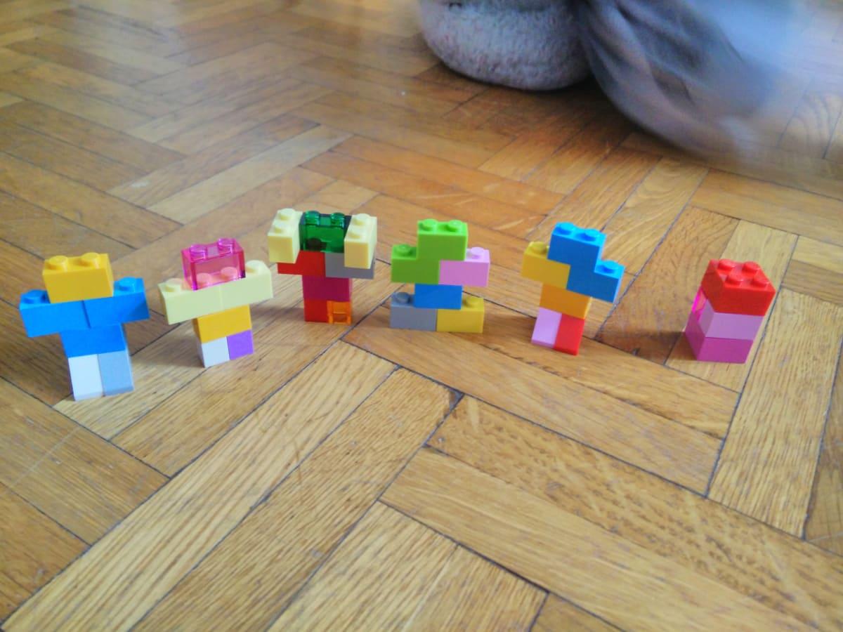 6 constructions en Lego, suggérant vaguement une forme humaine. Les briques et les couleurs utilisées varient.