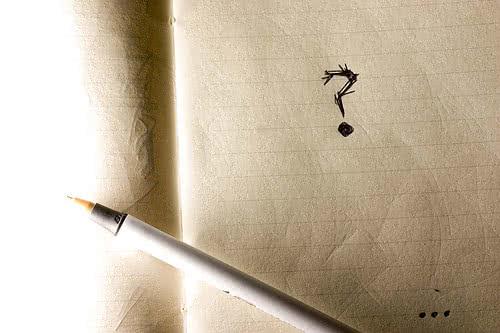 Un crayon écrit un point d'interrogation sur un carnet