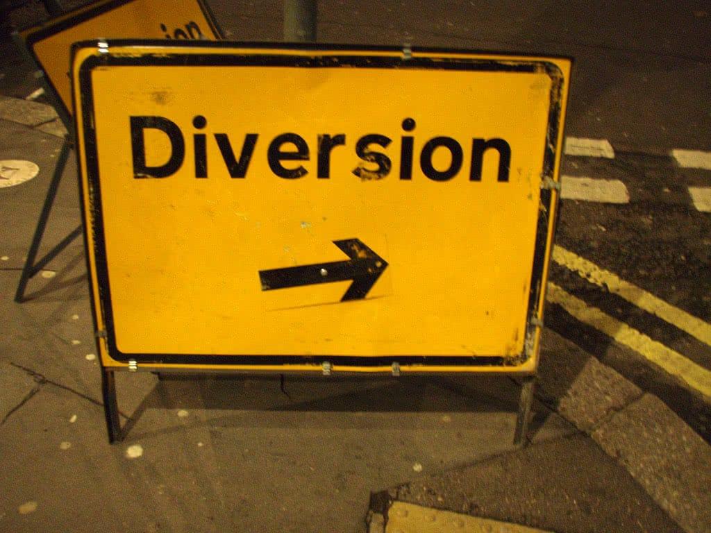 Un panneau jaune indiquant une diversion posé sur un trottoir.