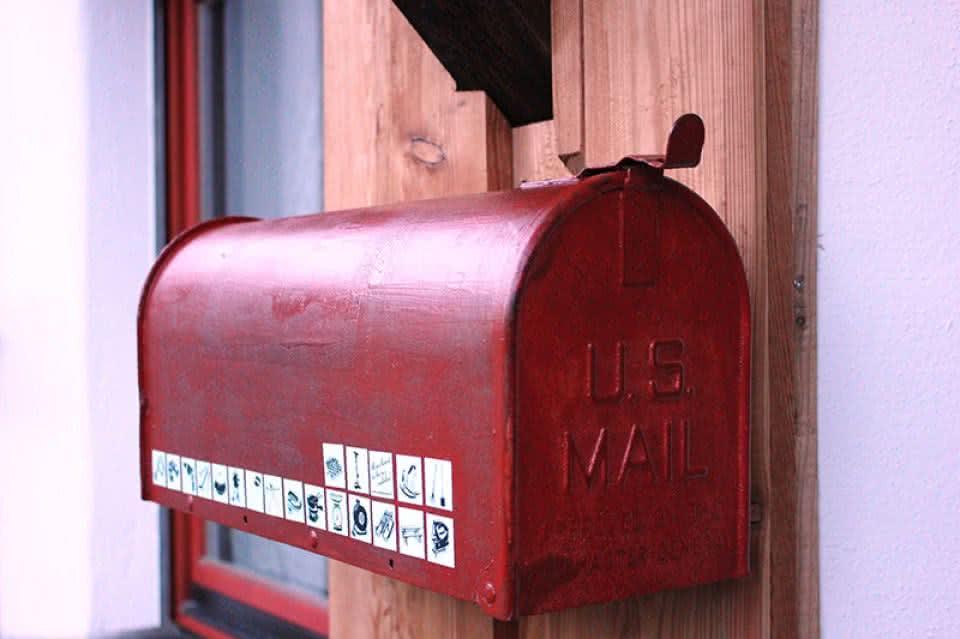 Une boite au lettre rouge sur laquelle des autocollants Pumpipumpe ont été apposés