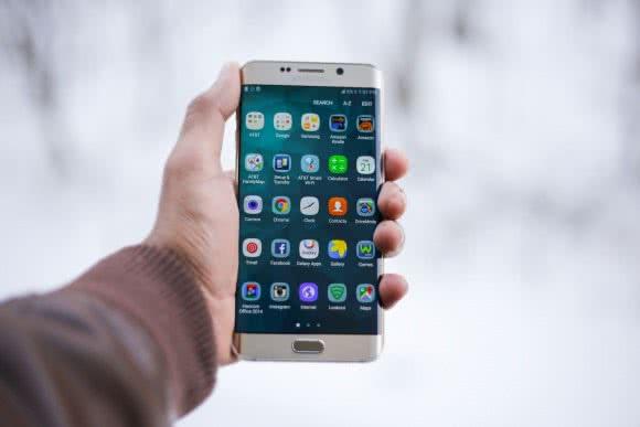 Une main tenant un téléphone de face. On y voit de nombreuses applications Android listées dans un menu.
