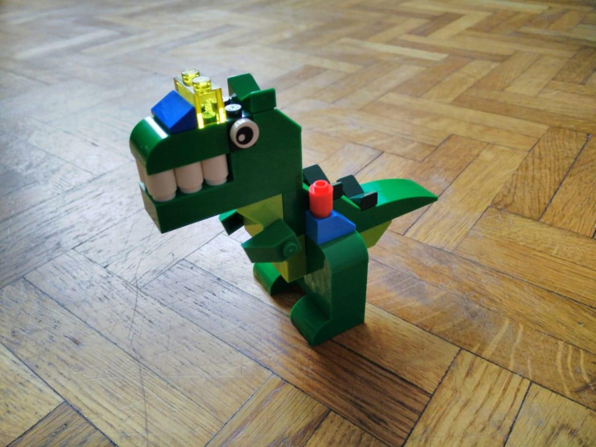 Une créature en Lego, proche du tyranosaure, mais avec un rictus très forcé et des éléments colorés sur la gueule et les cuisses, lui donnant l'aspect d'être hybride avec une machine.
