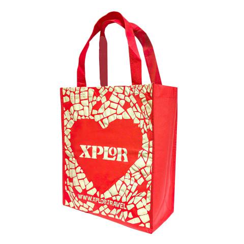 Bolsa Non-Woven impresa color rojo con logotipo Xplor Travel.