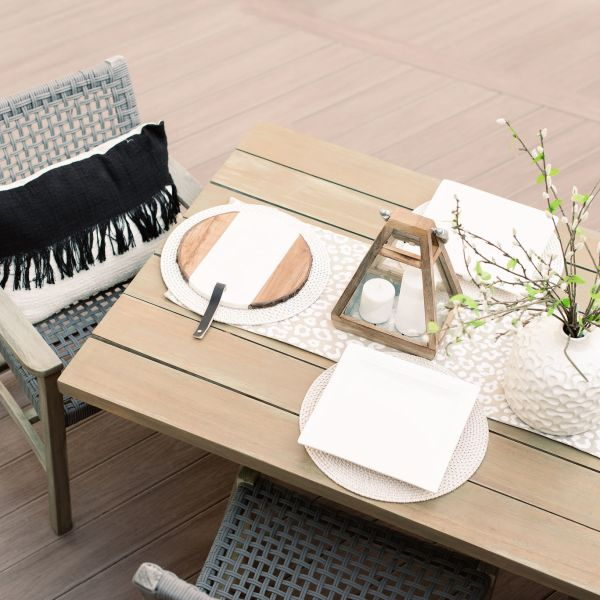 Composite deck furnished with wooden table and wicker chairs