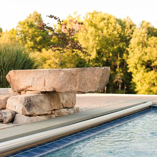 large natural stones decoratively stacked beside the pool