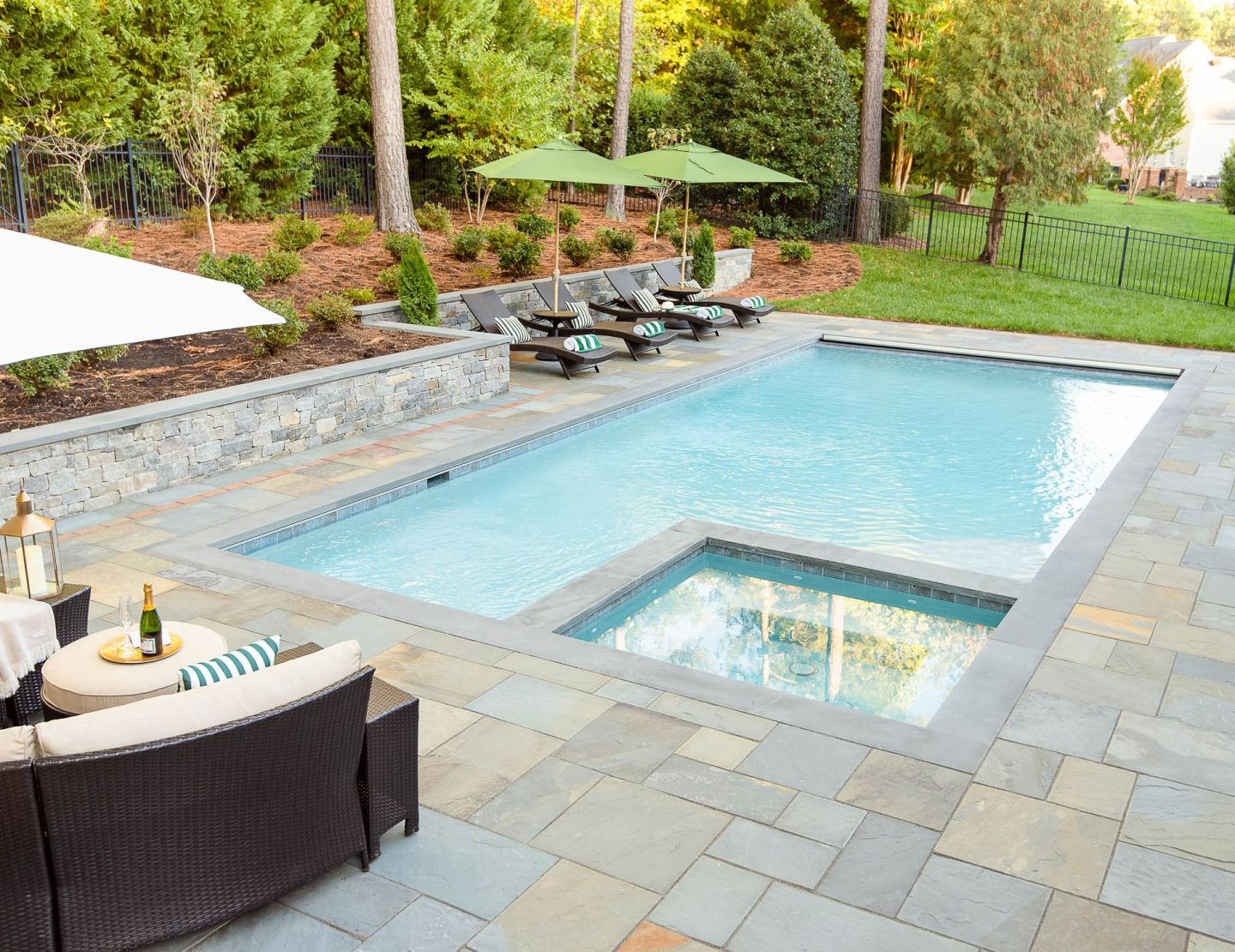 Pool and Hot Tub with stone patio and stone wall