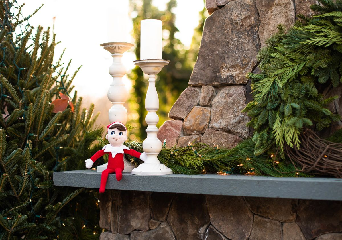 Elf on the shelf sitting on outdoor fireplace mantle