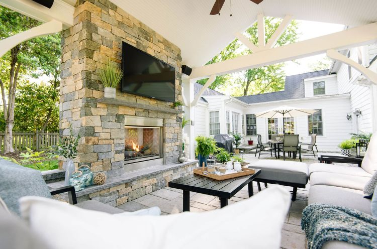 Backyard pavilion entertainment area featuring a stone wall to house the TV and fireplace