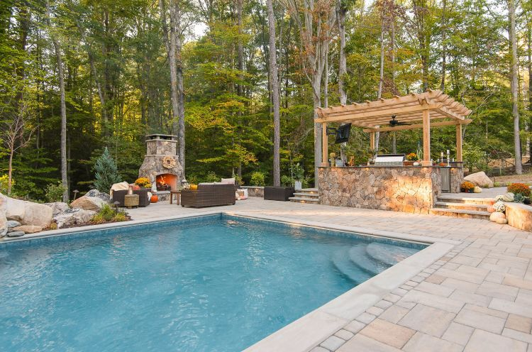 Outdoor space featuring a kitchen under a pergola, fireplace and fiberglass pool.