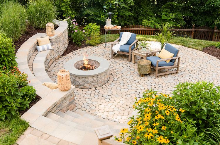 Step down into a backyard patio hardscaped with pavers, built-in fire pit with retaining wall benches